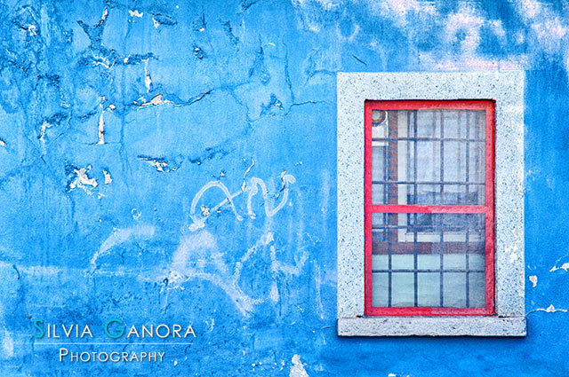 Window with red frame on blue wall