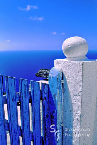 Greek blue gate with wondering clouds - ©Silvia Ganora Photography - All Rights Reserved