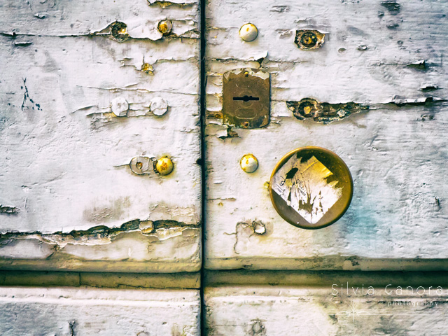 Cracked and peeling door detail with keyhole and doorknob - ©Silvia Ganora - All Rights Reserved