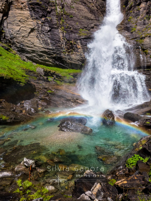 Waterfall and pool of water with rainbow