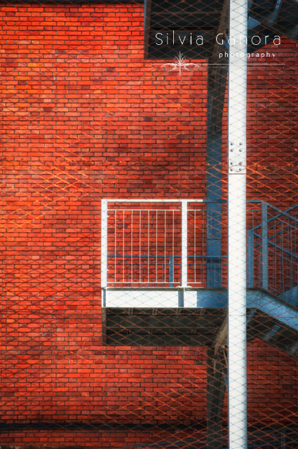 Fire escape stairs behind wire mesh and against vivid orange brick wall