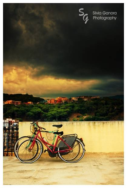 Two colorful bicycles on a terrace overlooking a stormy sky with big dark clouds and maritime pines and houses on a hill. Shot in Messina, Sicily.