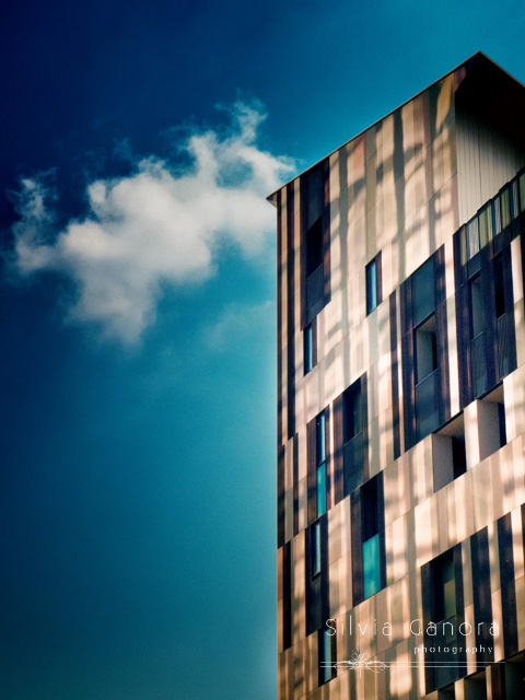 Moody shot of a modern skyscraper with blue sky and lonely cloud in the background- ©Silvia Ganora Photography - All Rights Reserved