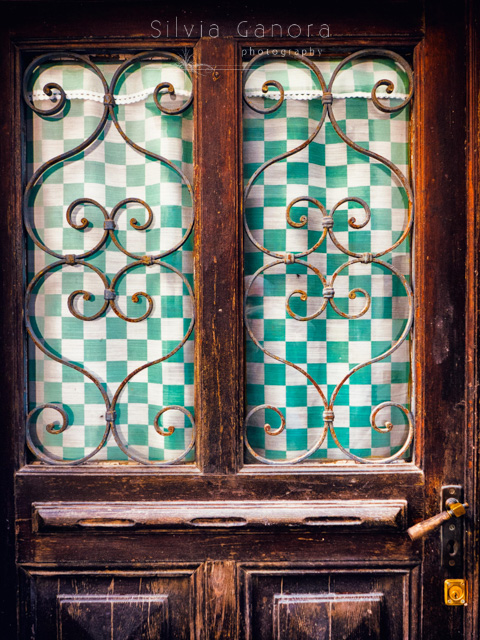 Old windowed door detail with checkered tent and ornate grate - ©Silvia Ganora Photography - All Rights Reserved