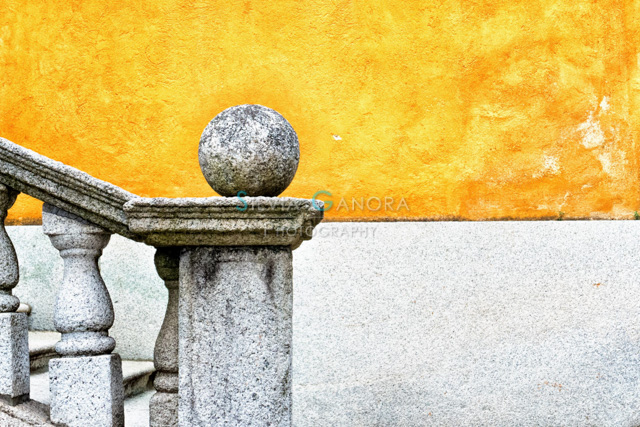 Minimal shot of a n old stone handrail with sphere on it and half yellow wall in the background - ©Silvia Ganora Photography - All Rights Reserved