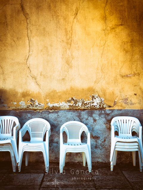 White plastick chairs stacked against decayed wall - ©Silvia Ganora Photography - All Rights Reserved