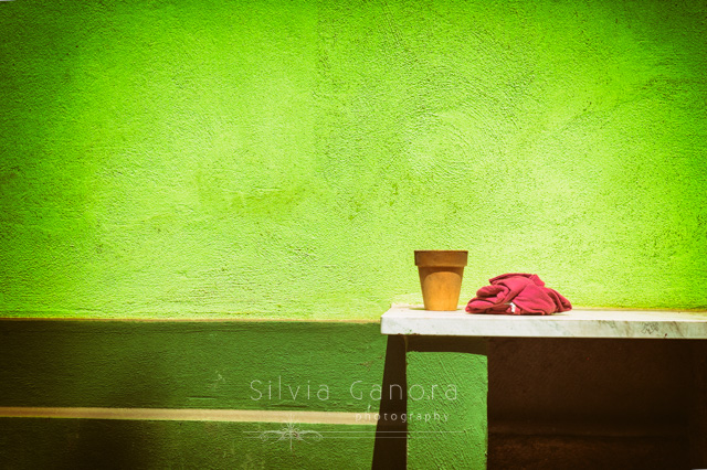 Minimalist shot of a vase and t-shirt on a marble table with bright green wall behind- ©Silvia Ganora Photography - All Rights Reserved