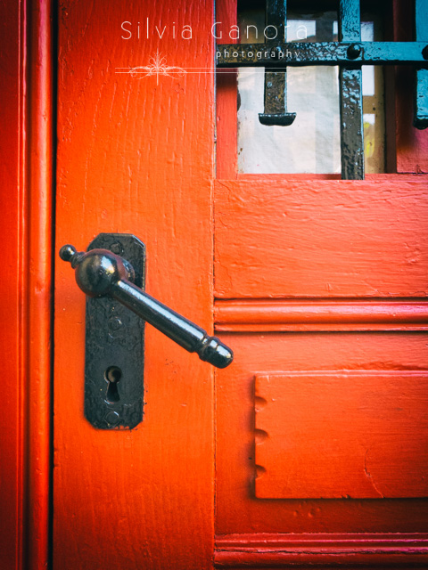 Red widowed door detail with black iron doorhandle- ©Silvia Ganora Photography - All Rights Reserved