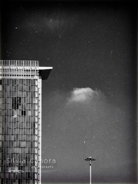 Surreal black and white shot of a modern building and a street lamp with sky and lonely fluffy cloud- ©Silvia Ganora Photography - All Rights Reserved