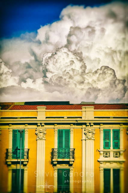 Italian house facade with yellow walls and balconies. Huge cloud formation over it.- ©Silvia Ganora Photography - All Rights Reserved