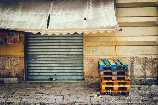 Closed shop exterior with tent over entrance and wooden racks on pavement. Entrance with rolling shutters down- ©Silvia Ganora Photography - All Rights Reserved