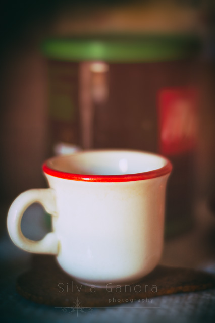 Close up shot of a coffee cup with red rim against a blurred background with out of focus coffee box- ©Silvia Ganora Photography - All Rights Reserved
