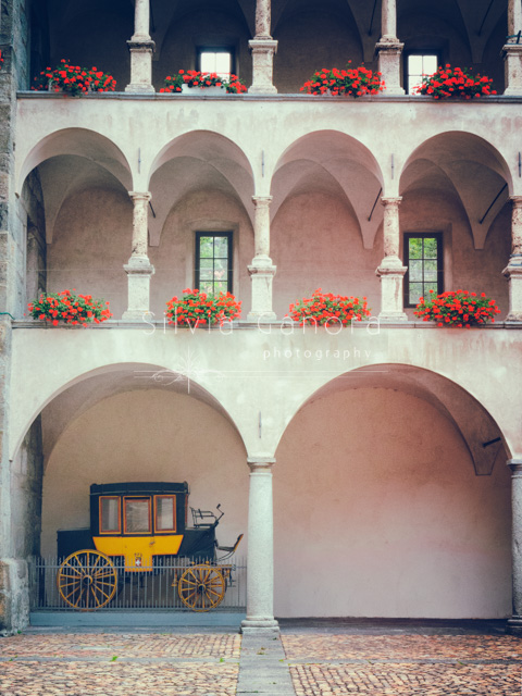 Old Swiss stagecoach under arched building with arched passageways and vases with geraniums- ©Silvia Ganora Photography - All Rights Reserved
