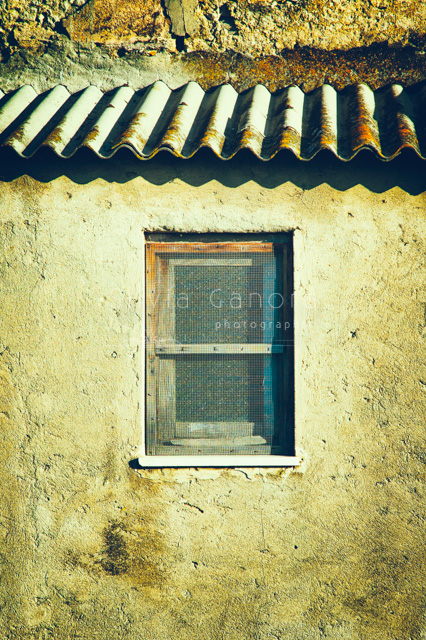 Decayed tiny window with improvised grate in front of it on a weatherd wall. Wavy roof tiles above it.- ©Silvia Ganora Photography - All Rights Reserved