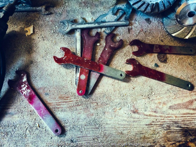 Spanners with red paint on them laying ona dirty wooden table with other mechanical instruments