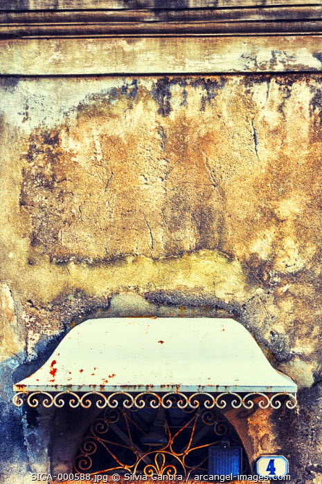 Ornate iron roofing over door. Door not visible. Decayed wall above it.- ©Silvia Ganora Photography - All Rights Reserved