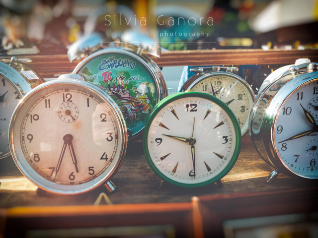 Vintage alarm clocks on display at a flea market with faded colors and light leaks- ©Silvia Ganora Photography - All Rights Reserved