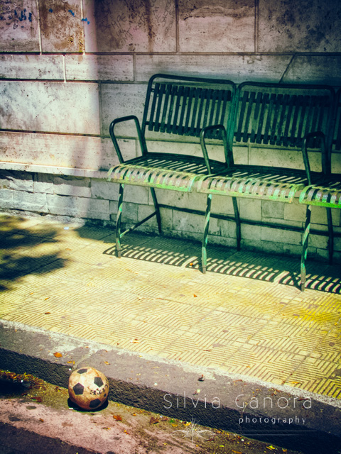Deflated soccer ball fotgotten near sidwalk with iron chairs inside a playground- ©Silvia Ganora Photography - All Rights Reserved