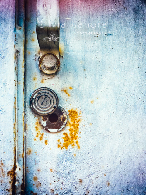Closeup shot of a round rusty keyhole and doorhandle on a rotten iron door- ©Silvia Ganora Photography - All Rights Reserved