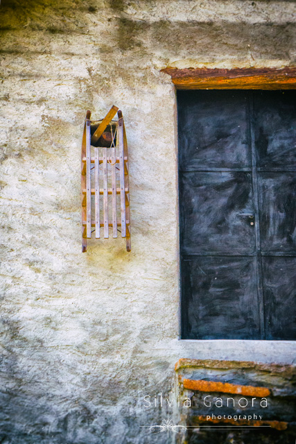 Old wooden sledge hanging form outside a house wall with iron door and steps- ©Silvia Ganora Photography - All Rights Reserved