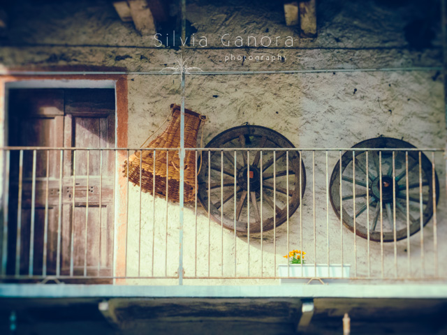 Old balcony with wooden wheels and conic wicker basket on the wall- ©Silvia Ganora Photography - All Rights Reserved