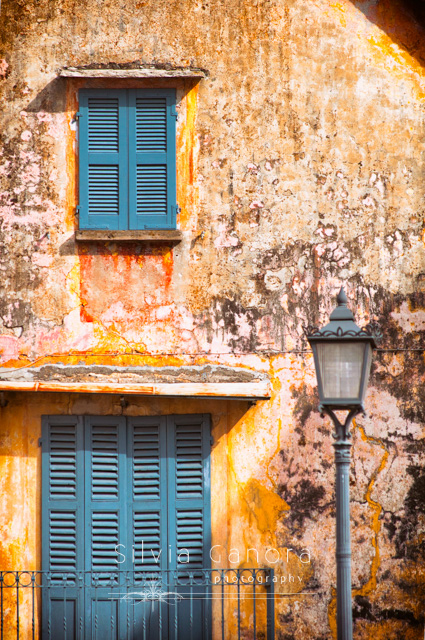 Weathered house facade with windows and closed shutters and street lamp- ©Silvia Ganora Photography - All Rights Reserved