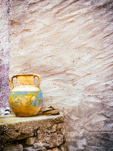 Weathered amphora left on a low stone wall with grungy wall behind- ©Silvia Ganora Photography - All Rights Reserved