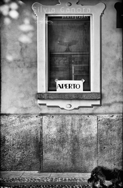 Black and white shot of an Italian shop window with Open sign taped on it. Cobbled street and back of a dog leaving the scene on the lower right side- ©Silvia Ganora Photography - All Rights Reserved