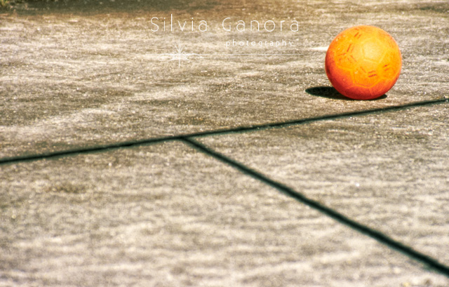Orange ball abandoned on sidewalk with shadows of two lines.- ©Silvia Ganora Photography - All Rights Reserved