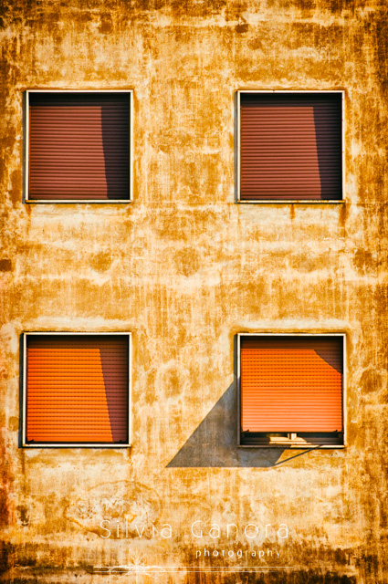 Four square windows on a weathered wall. Three of them have rolled down shutters- ©Silvia Ganora Photography - All Rights Reserved