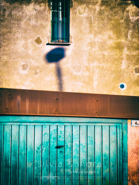 Garage door with window with grate and shadow on wall- ©Silvia Ganora Photography - All Rights Reserved
