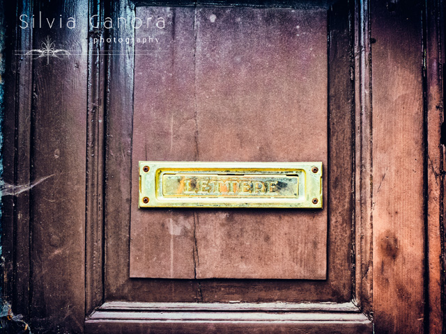 Closeup shot of an iItalian mailbox on a decayed wooden door- ©Silvia Ganora Photography - All Rights Reserved