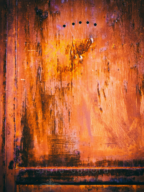 Closeup shot of a rusty iron door with scratches and five holes in it- ©Silvia Ganora Photography - All Rights Reserved