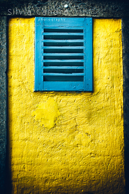 Tiny window on yellow wall with closed shutter - Copyright Silvia Ganora Photography