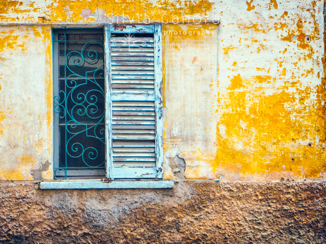 Decayed wall with rotten window with single shutter. Window hadìs ornate grate.- ©Silvia Ganora Photography - All Rights Reserved
