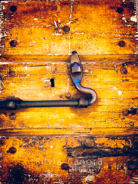 Closeup shot of an iron lock on a weathered wooden door with keyhole - Copyright Silvia Ganora Photography