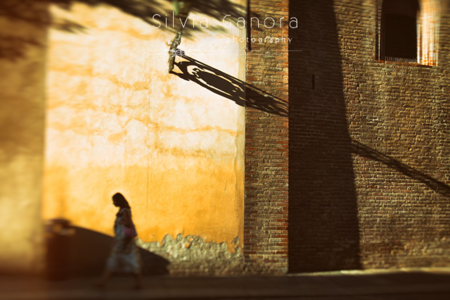 Italian woman walking in a city street with long shadows- ©Silvia Ganora Photography - All Rights Reserved