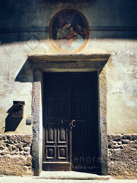 Old Italian door with painting on wall above it- ©Silvia Ganora Photography - All Rights Reserved