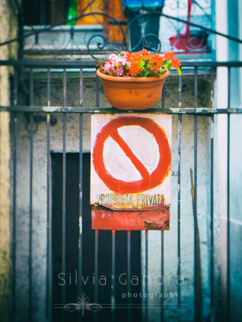 Gate with private property sign painted on a metal plate and with vase of flowers. Italian language Copyright - Silvia Ganora Photography