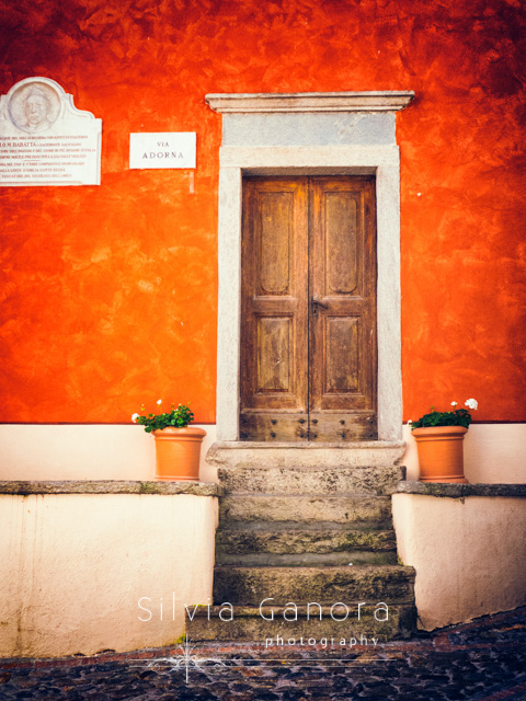 Wooden Italian door with colorful wall and steps with vases- ©Silvia Ganora Photography - All Rights Reserved