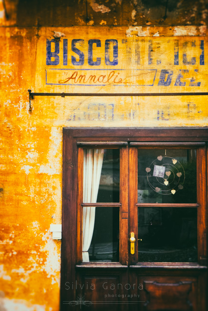 Old Italian buiscuit shop with wooden windowed door and decayed sign on wall - ©Silvia Ganora Photography - All Rights Reserved