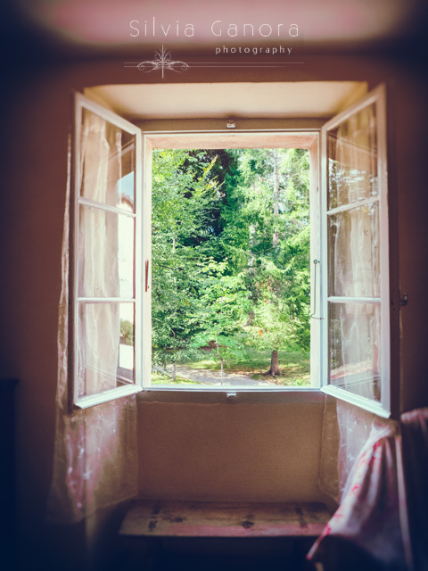 Interior shot of an open window with framed trees outside. Old wooden stool below it - ©Silvia Ganora Photography - All Rights Reserved