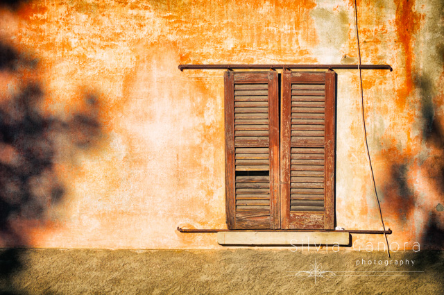 Old window with closed shutters on a wall with tree shadows - ©Silvia Ganora Photography - All Rights Reserved