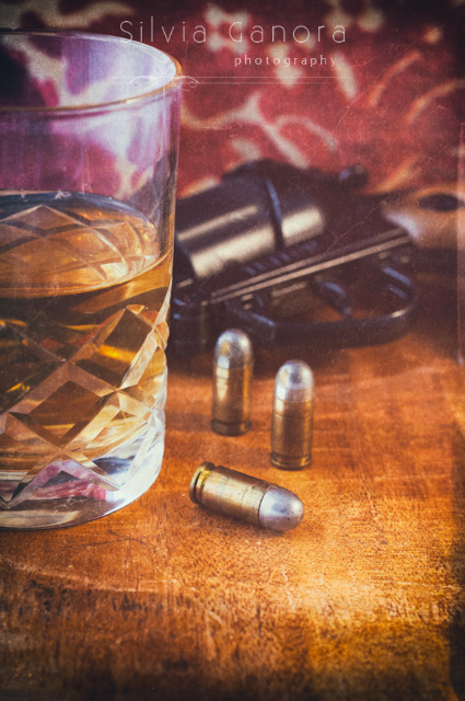 Closeup shot of three bullets on a table with glass with whisky and old gun in the background - ©Silvia Ganora Photography - All Rights Reserved