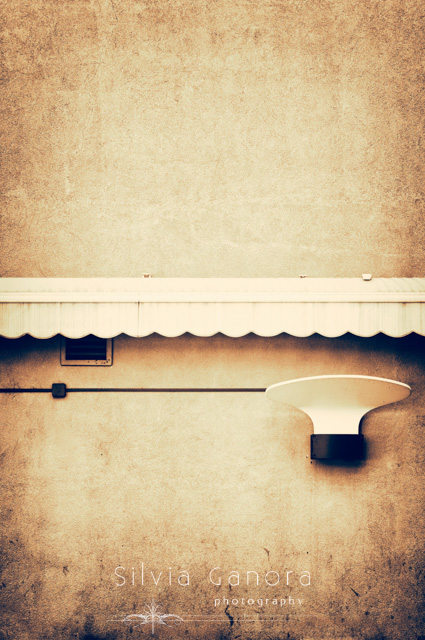 Minimalistic shot of a white lamp and white tent on a wall - ©Silvia Ganora Photography - All Rights Reserved