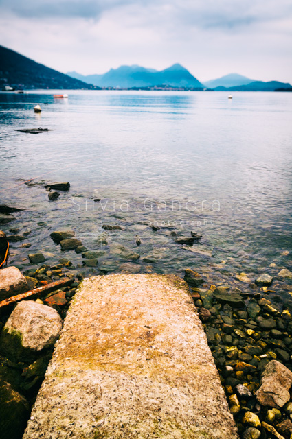 A cement pathway to the lake waters with mountains in the distance - ©Silvia Ganora Photography - All Rights Reserved