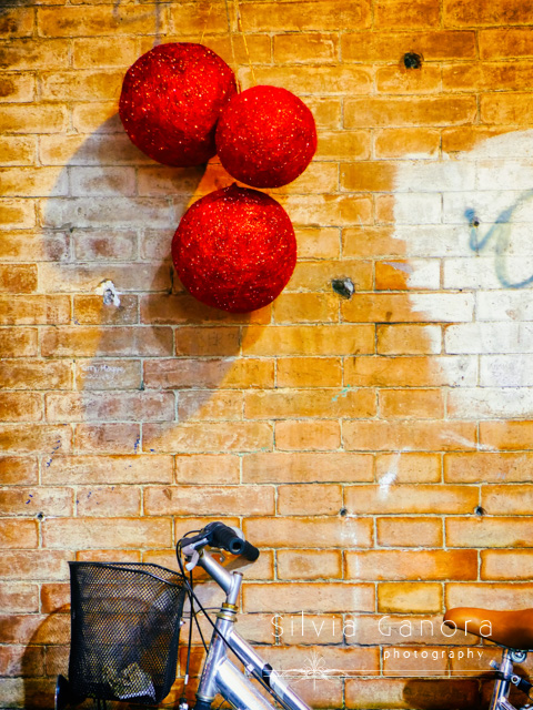 Three red spheres hanging on a wall and a bicycle detail - ©Silvia Ganora Photography - All Rights Reserved