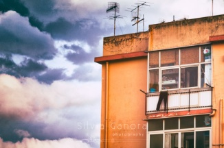 Detail of a building with trousers hanging out to dry and dramatic sky - ©Silvia Ganora Photography - All Rights Reserved