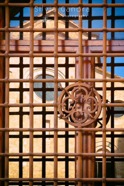 Italian church reflecting in a window with ornate gate - ©Silvia Ganora Photography - All Rights Reserved