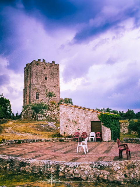 Old turret with dramatic sky and plastic chairs in front of it - ©Silvia Ganora Photography - All Rights Reserved
